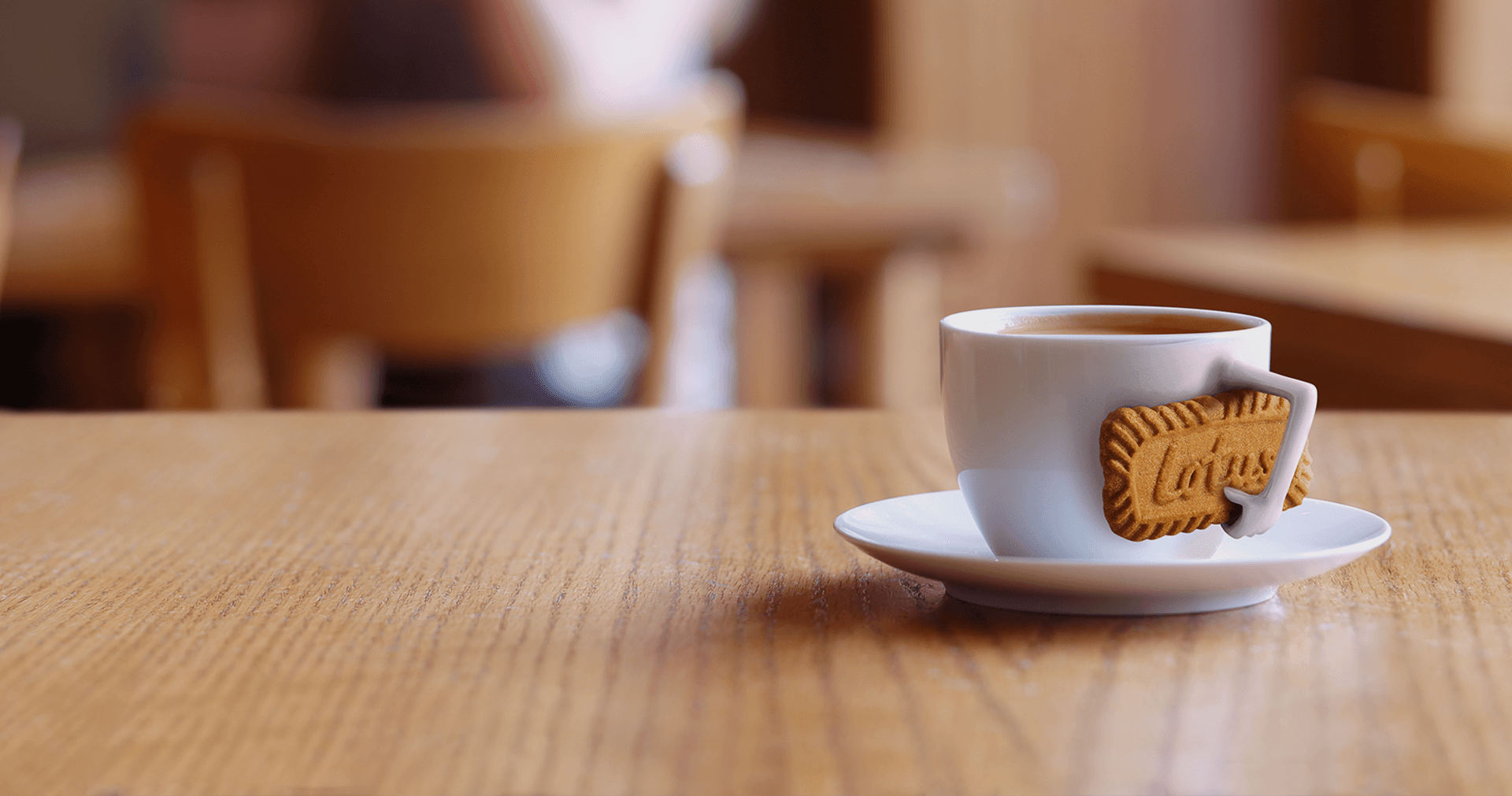 A cup of coffee holding a biscoff cookie